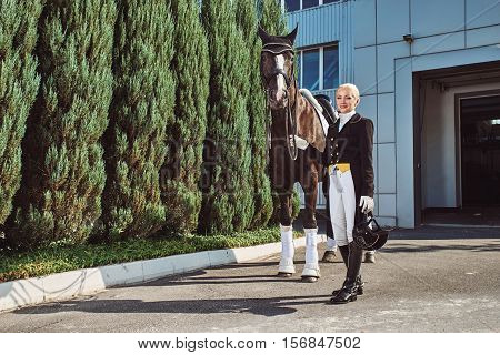woman jockey with his horse in uniform for Dressage