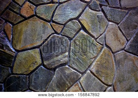 A full frame image of a mosaic stone wall.