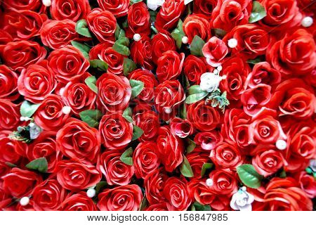 A group of plastic red roses with a central focal point.