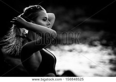Beautiful brunette girl in white posing on a windy beach in monochrome