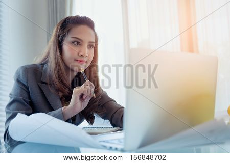 Young business woman using laptop and thinking her building home project plan while sitting at desk on office with drawing pape