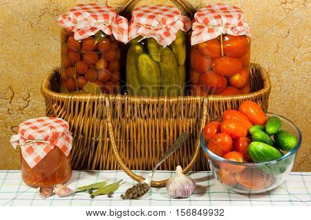 Homemade Canned Vegetables (Tomatoes Cherry Cucumbers Tomatoes) In Glass Jar On Wicker Basket Fresh Vegetables (Tomato Cucumbers) In Glass Bowl Garlic Bay Leaf Metal Spoon With Allspice Tomato Sauce On Wooden Table. Top View.