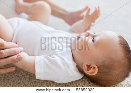 child, childhood, babyhood and motherhood concept - close up of happy little baby and mother hands