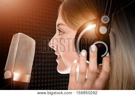 Female Voice Talent in Recording Studio. Girl Recording Voice Over For Radio Commercial. Young Girl in Her 20s and the Shiny Metallic Pro Microphone.