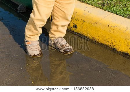 A small child standing in a puddle of water. His shoes wet. You only see the legs.