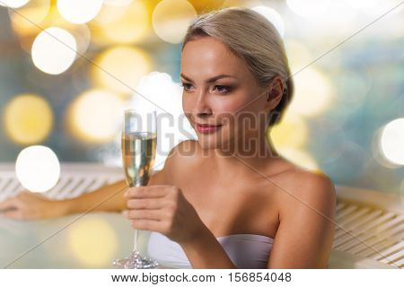people, beauty, spa, healthy lifestyle and relaxation concept - beautiful young woman wearing bikini swimsuit sitting with glass of champagne in jacuzzi at poolside over holidays lights background
