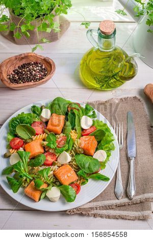 Salad With Salmon And Vegetables On Old Wooden Table
