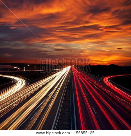 Speed Traffic at Sundown Time - light trails on motorway highway at night,  long exposure abstract urban background