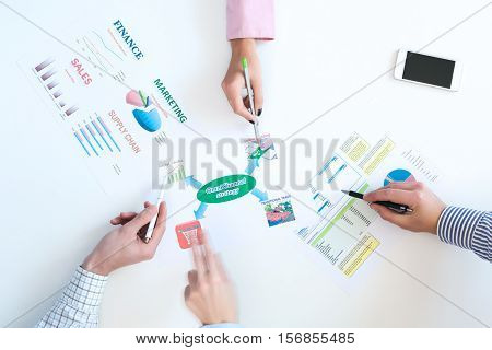 Top View of Business Meeting Paper Charts on White Desk Hands of People discussing pointing with pens one Person Hand blurred emotional Gesture Move