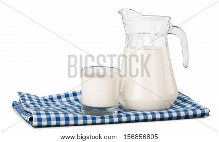 A glass of milk and a milk jug on plaid tablecloth