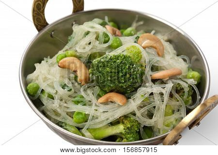 Vegan and vegetarian dish, spicy rice vermicelli with broccoli and cashew in bowl. Indian cuisine with herbs, healthy meal closeup isolated on white background. Eastern local cuisine restaurant food.