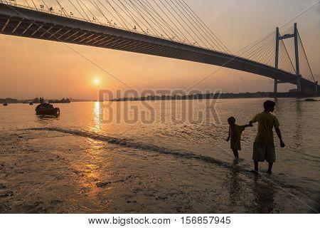Two street kids have fun on the Hooghly river bank at Princep ghat, close to Vidyasagar setu (bridge) at sunset time (silhouette). Photograph taken at Princep ghat, Kolkata, India on November 14, 2016.