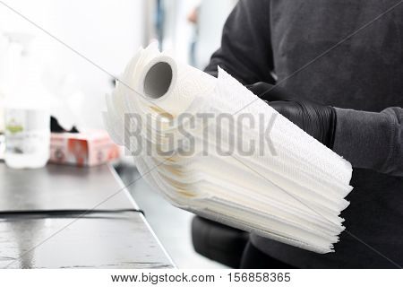 A tattoo artist preparing disposable paper towels.  Hygiene in the tattoo parlor.
