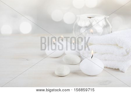 Spa resort therapy composition. Burning candles stones towel abstract lights