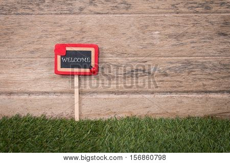 Welcome signpost in beautiful greensward on wooden blackground