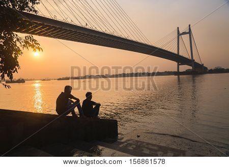 Two friends enjoy the sunset view on river Hooghly with Vidyasagar setu (bridge) at the backdrop at Princep Ghat, Kolkata, India. Photograph taken at Princep Ghat on November 14, 2016.