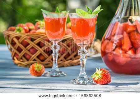 Homemade Strawberry Liqueur With Mint On Old Wooden Table