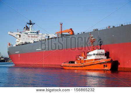 A orange tugboat assisting a large oil tanker.