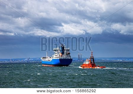 Tanker ship is assisted by a tug boat in the port.