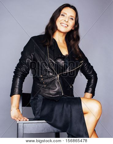 pretty brunette confident stylish real mature woman sitting on chair in studio, sexy on gray background wearing leather jacket close up