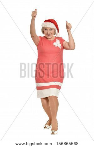 Full lenght portrait of happy  senior woman in Santa hat showing thumbs up isolated on white background