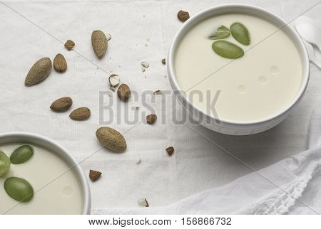 Two white bowls with white garlic soup with three pieces of grapes on a white tablecloth with raw almonds.