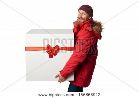 Christmas, x-mas, winter gift concept. Man wearing red winter jacket carrying huge heavy gift box with red bow, isolated on white