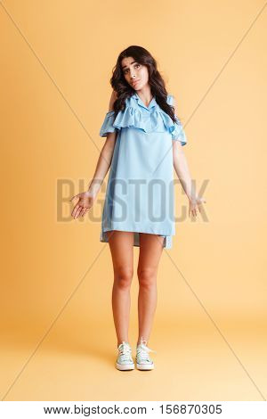 Full length portrait of a young woman shrugging shoulders isolated on a orange background