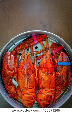 Overhead view of Maine Lobster in the iron steamer on a dark wooden table