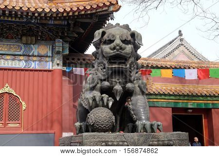 BEIJING - FEBRUARY 25, 2016: Bronze imperial lion at the gate of Lama Temple Yonghe Lamasery. It is one of the largest and most important Tibetan Buddhist monasteries in the world in Beijing, China.