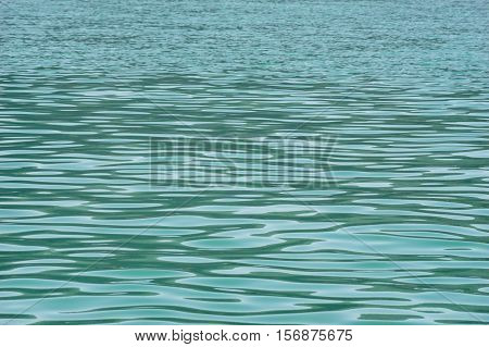 Ripple on turquoise lake water natural background