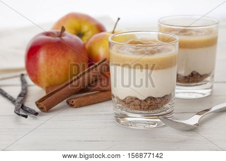 winter dessert with vanilla-flavored cream on cookie crumbles and a topping of roast apple sauce with cinnamon in glasses
