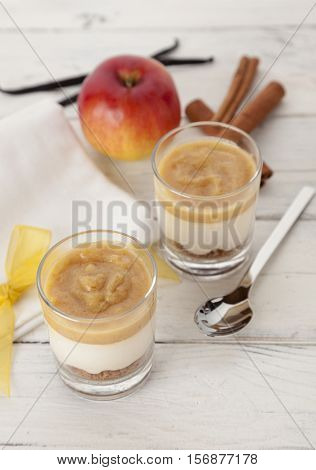 Dessert with cinnamon-flavored applesauce, vanilla-flavored cream and cake crumbles in glasses, arranged with ingredients on table