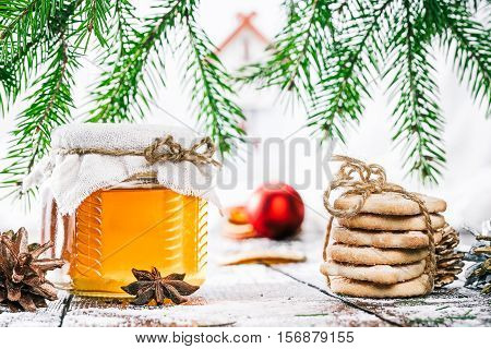 Honey in closed and tied glass can and christmas cookies stack under evergreen branches