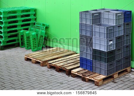Store unloading. Plastic containers for storage and transportation of products on wooden pallet on the background of green metal panel wall.