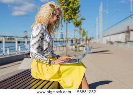 Modern woman sitting on the bench outside and working on computer