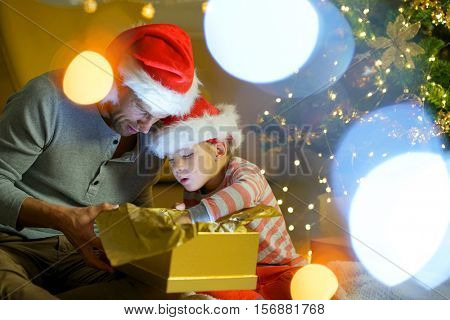 Daddy and little boy opening christmas gift