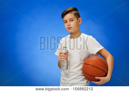 Adorable 11 year old boy child with basketball ball drinking water on blue background.