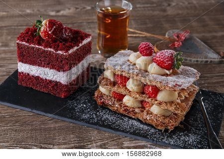mille feuille dessert sweet slice  red velvet cake with white frosting is garnished with strawberries
