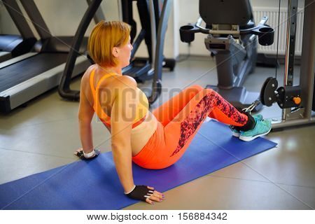 Middle-aged woman in orange does exercise in modern gym, shallow dof