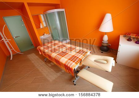 Orange room with table for massage, aromatherapy and shower cabin