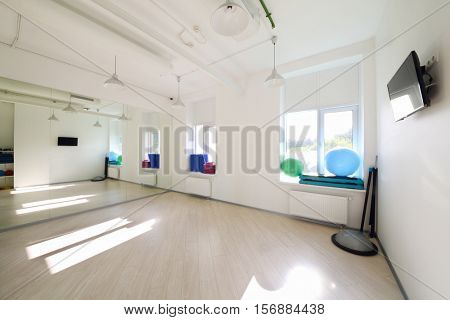 Empty light room for fitness classes with fitballs, displays and other equipment
