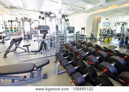 Modern gym with new shiny fitness equipment, big mirror, dumbbell set for sport training
