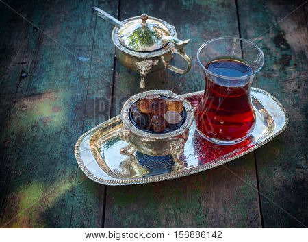 Black tea Turkish glass with slices of sugar on a silver platter vintage toning
