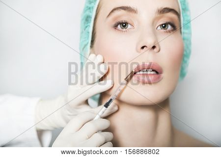 Doctor aesthetician makes hyaluronic acid beauty injections in lips to make lips correction and augmentation of female patient in a green medical cap