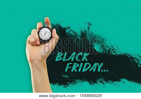 The male hand holding a stopwatch against a yellow background. Black Friday sale - holiday shopping concept