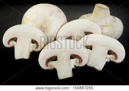fresh champignon mushrooms at on wooden background