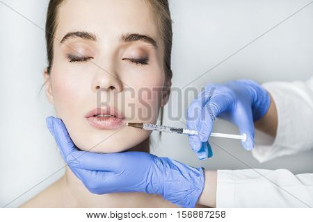 Doctor aesthetician in blue medical gloves makes hyaluronic acid beauty injections in lips to make lips correction and augmentation of female patient