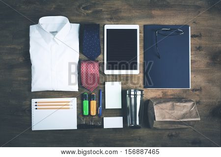 Business objects on the desk, including digital tablet, shirt, ties, lunch box, paper and pencils, top view, toned photo