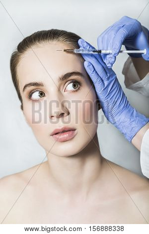 Doctor aesthetician in blue medical gloves makes hyaluronic acid beauty injections in the forehead of female patient